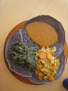 A platter of injera topped with cabbage, shiro, and gomen that I made for the yahelnikim